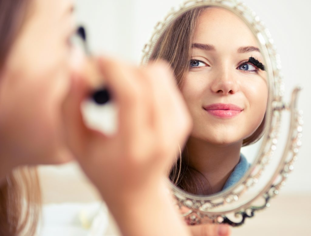 Beauty model teenage girl looking in the mirror and applying mascara make up. Beautiful young woman apply makeup, 5 Ways to Not Feel Rushed in the Morning