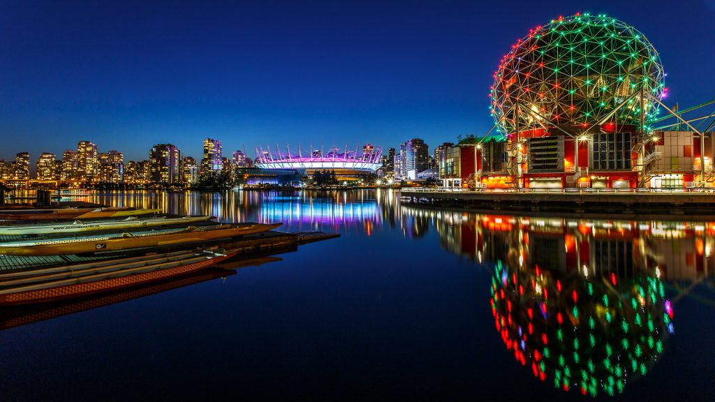 Science World and BC Olympic Place illuminated at night in Vancouver Canada
